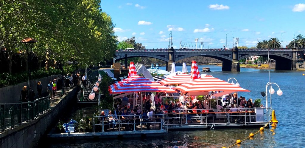 A long bar on the water with red and white umbrellas
