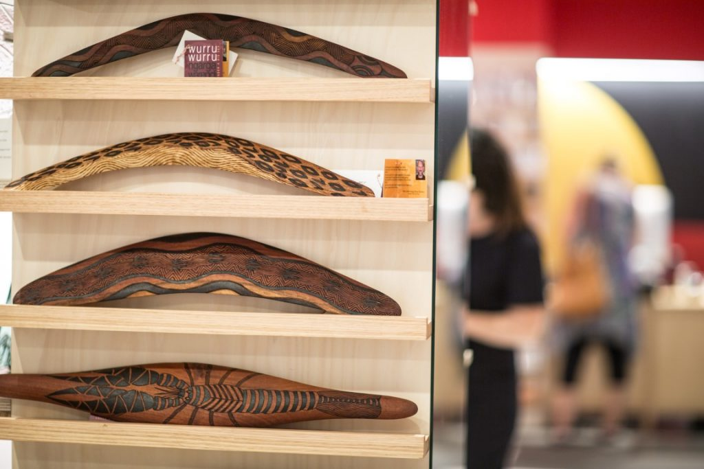 Shelves displaying three boomerangs and one other wooden aboriginal artefacts