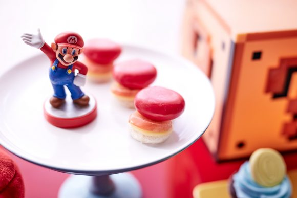 A Super Mario figurine sitting on a plate of macarons