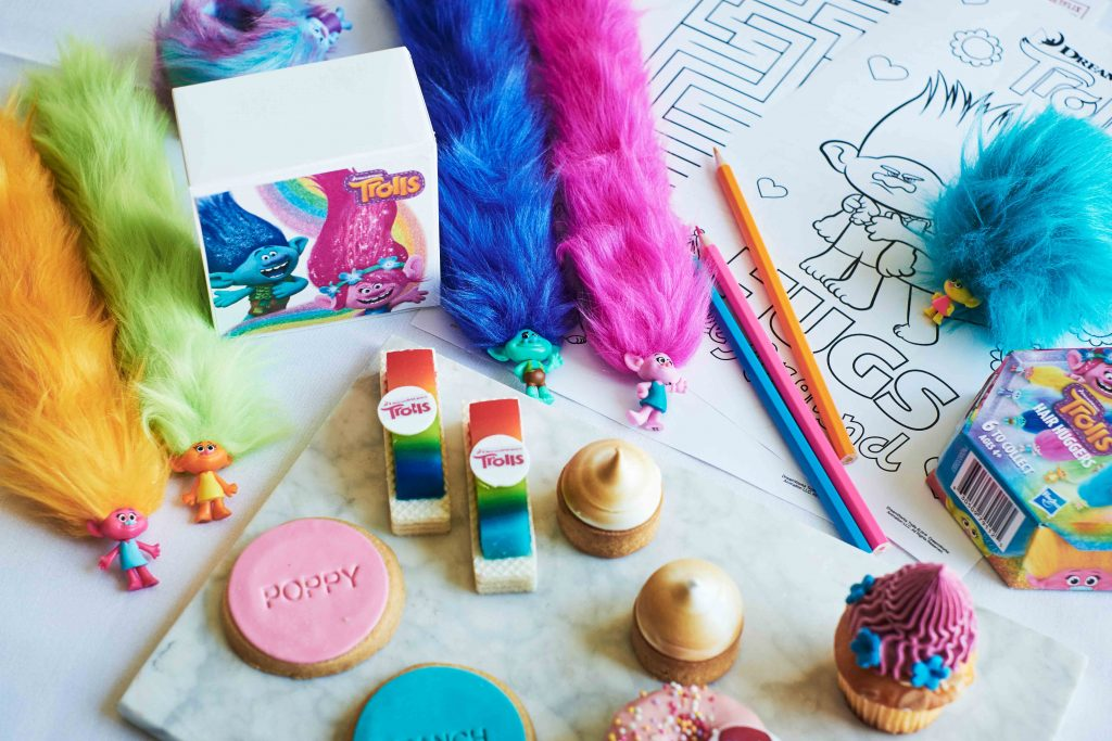 Troll toys, coloured biscuits and pastries and a colouring in pattern and pencils on a table