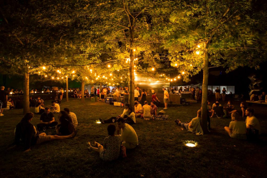 An outdoor garden at night with bright fairy lights hanging from the trees