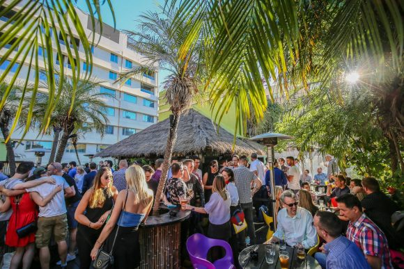 Crowd of people talking and drinking in a tropical style rooftop bar.