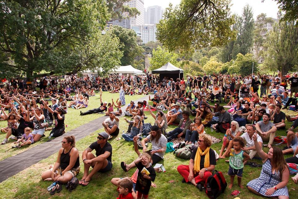 A crowd of people sitting on the grass in a park watching a concert
