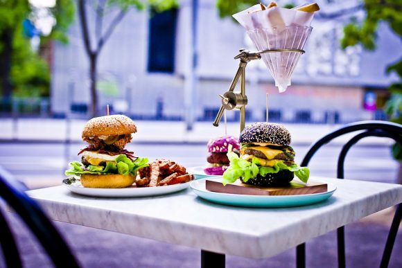 Two burgers on an outdoor table, with a cone of fries held above them by a copper stand