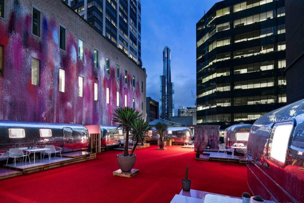 A red carpet rooftop with silver caravans