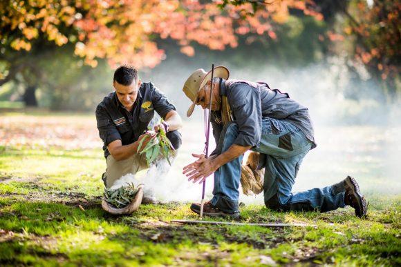 Two Aboriginal men preparing for a smoking ceremony