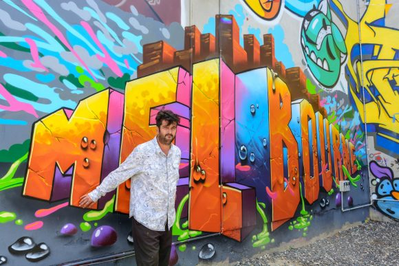 A man standing in front of a mural with the word Melbourne written on it
