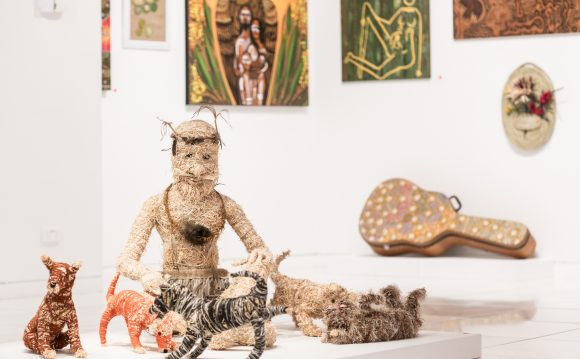 Straw sculptures of a man surrounded by animals