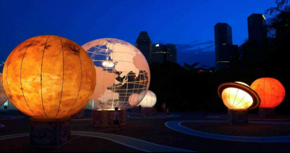 A series of illuminated globes that look like planets in a park at night