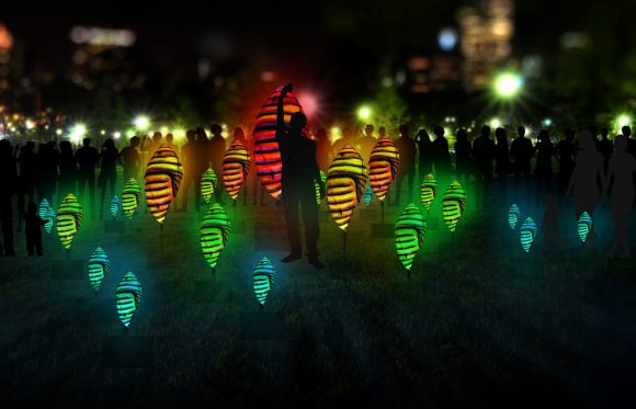 A person touching an illuminated sculpture at night, surrounded by many other illuminated sculptures and a crowd of people.