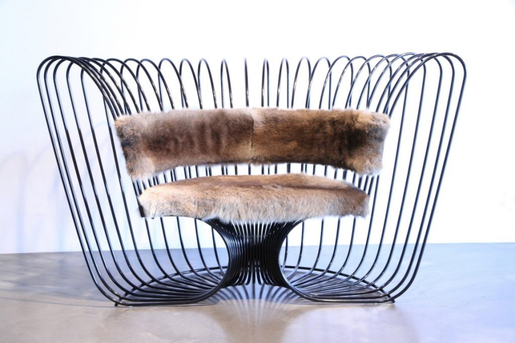 A large wire chair with a fur seat and back rest, on a marble floor with a white wall behind it