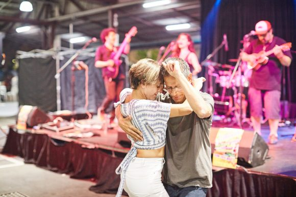 A couple dancing in front of a band on stage