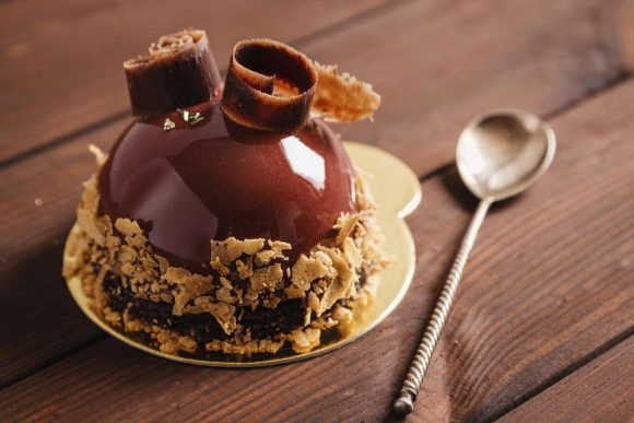 French mousse cake covered with chocolate glaze on wooden background. Modern european cake pastry. Shallow focus