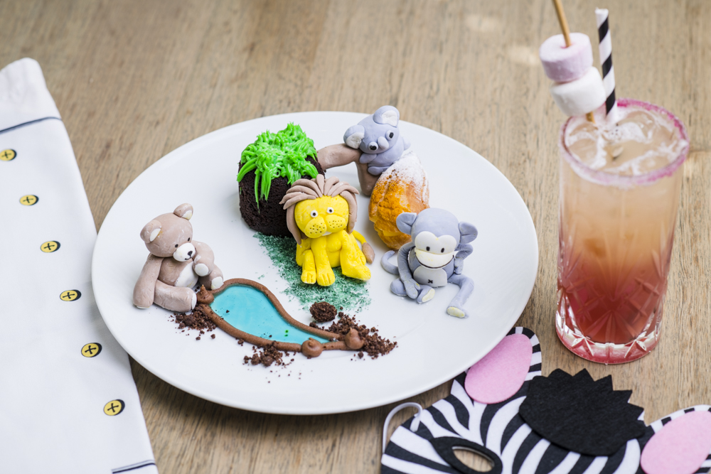Cakes shaped like zoo animals on a white plate next to a glass of iced tea