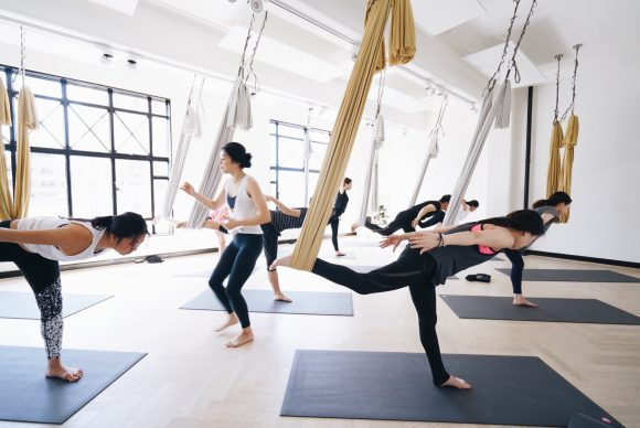 People doing yoga using hammocks hanging from the ceiling