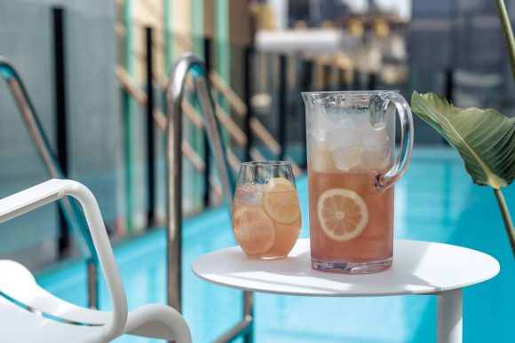 A glass and a jug of cocktails next to a pool