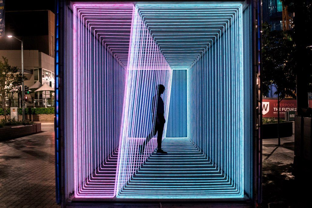 A person standing among neon lights