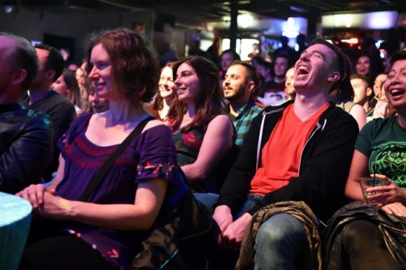 People sitting in a theatre laughing