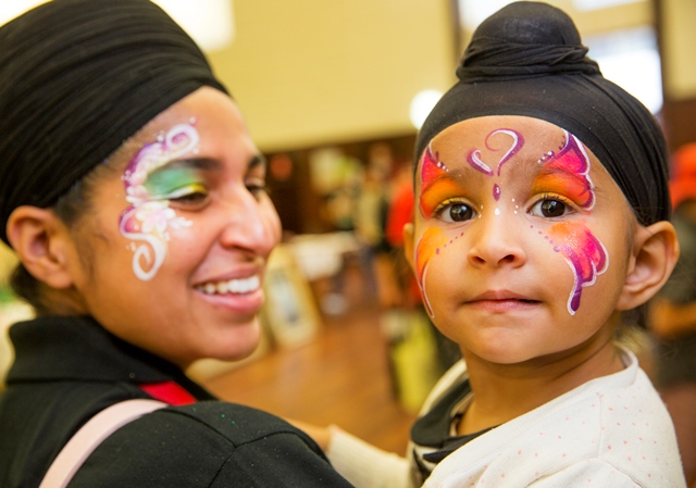 Woman and her toddler looking happy wearing turbans and butterfly face paintings