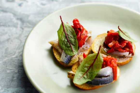 Three pieces of bread with sardines, sun dried tomatoes and herbs on a plate