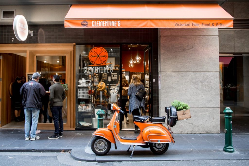An orange vespa parked outside a shop