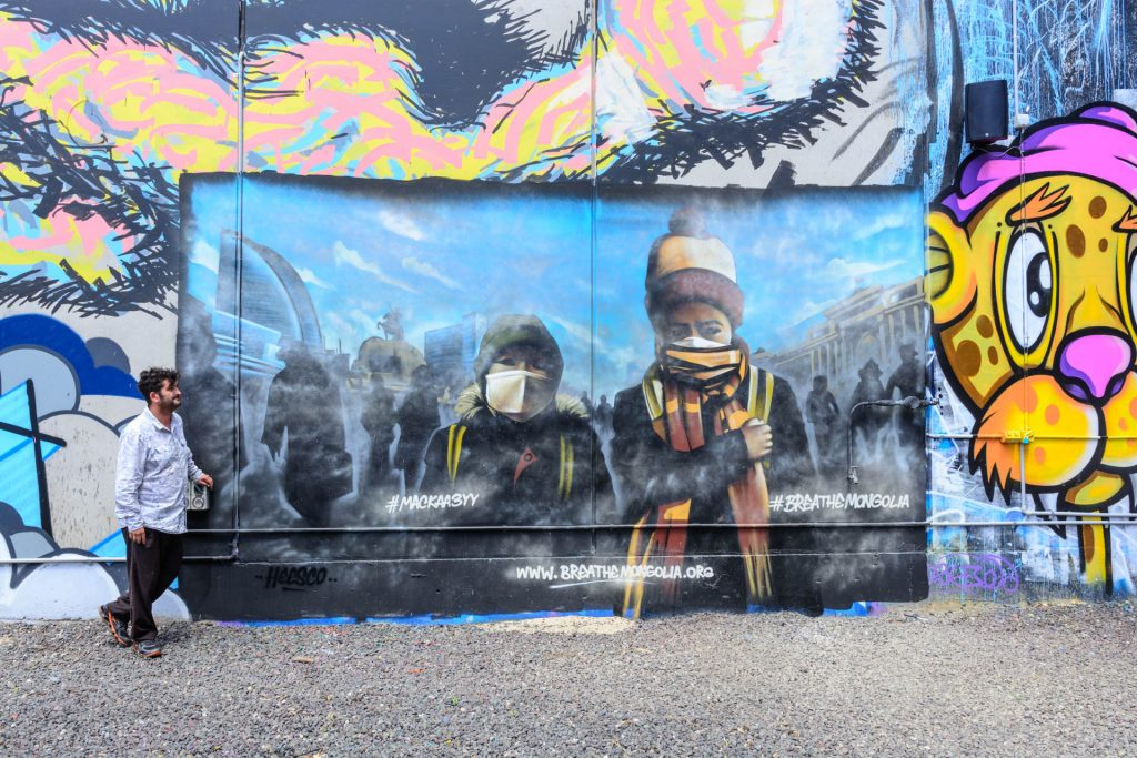 A street art mural featuring two children in scarves and beanies