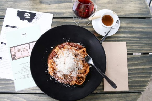 An aerial view of a bowl of pasta topped with cheese and bolognaise sauce, with a red wine and a coffee on a table