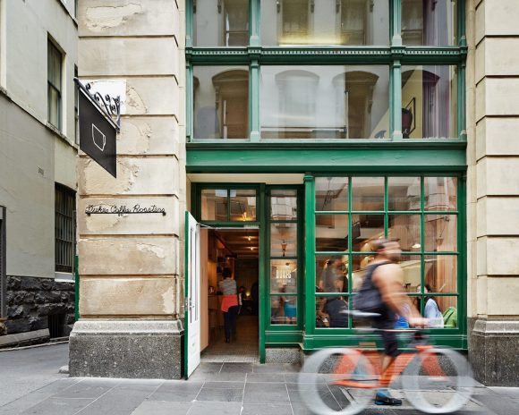 A man cycling past a city cafe in an old building
