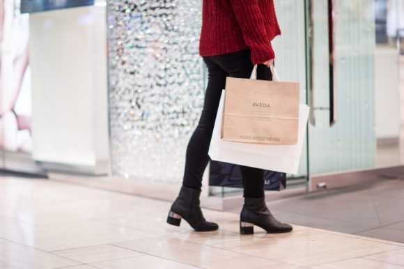 A person walking in a shopping centre and holding shopping bags