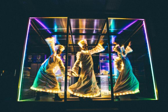 Three people dressed as angels inside a glass box, with colourful lighting.