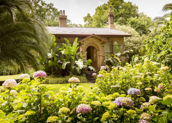 A cottage surround by green lawns, flowers and leafy trees