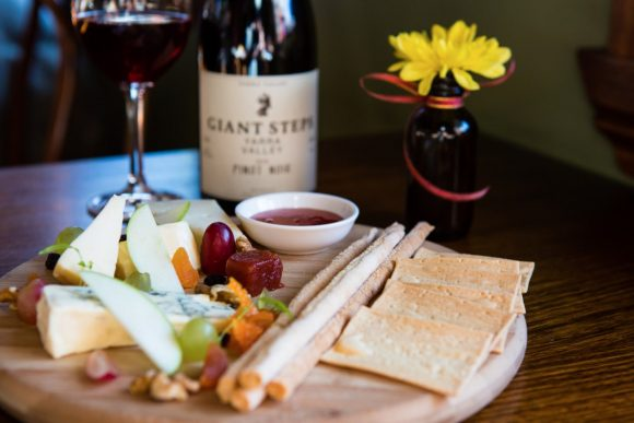 A wooden platter with crackers, fruit and cheese on it in front of a bottle of wine