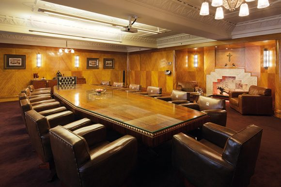 A large meeting table in a wood-paneled boardroom