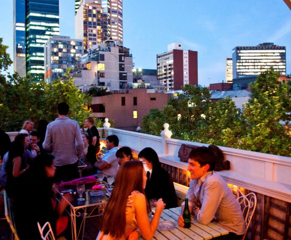 A couple sitting at a table in a busy rooftop bar with the city skyline in the background