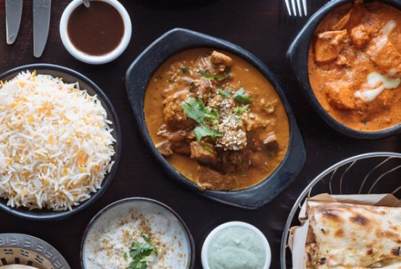 An indian feast with curries, naan and rice on a table
