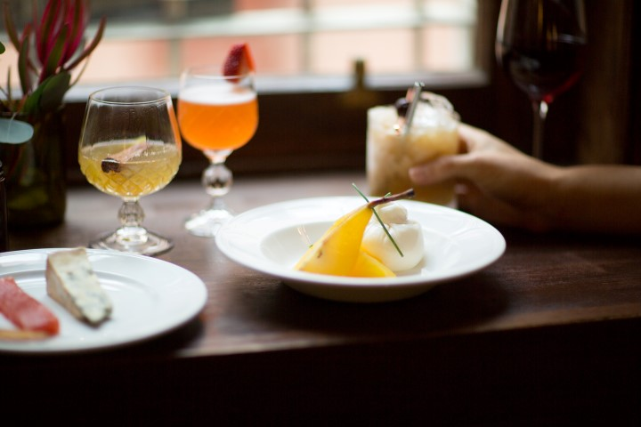 A hand holding a cocktail on a window ledge with two other cocktails and two plates of cheese near by