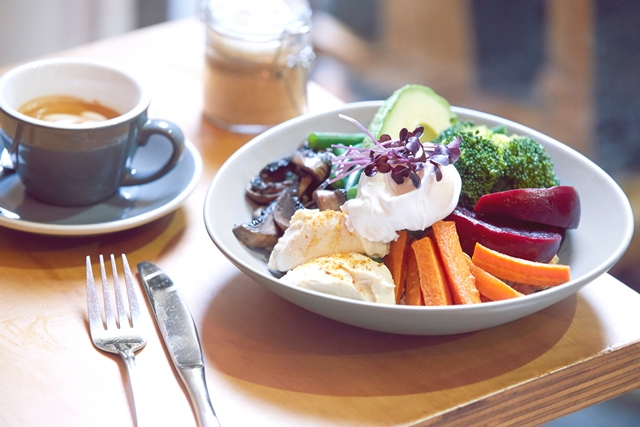 Table setting featuring bowl of colourful mixed vegetables with pouched eggs and garnishes, as well as a black coffee and knife and fork on the side