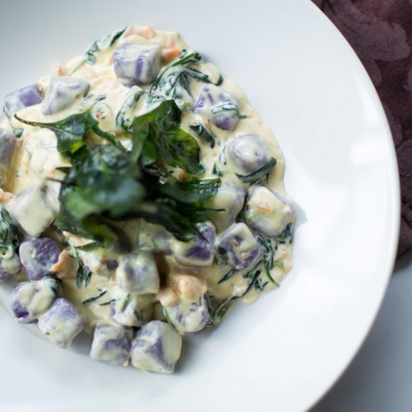A plate of gnocchi with a creamy sauce mixed through it