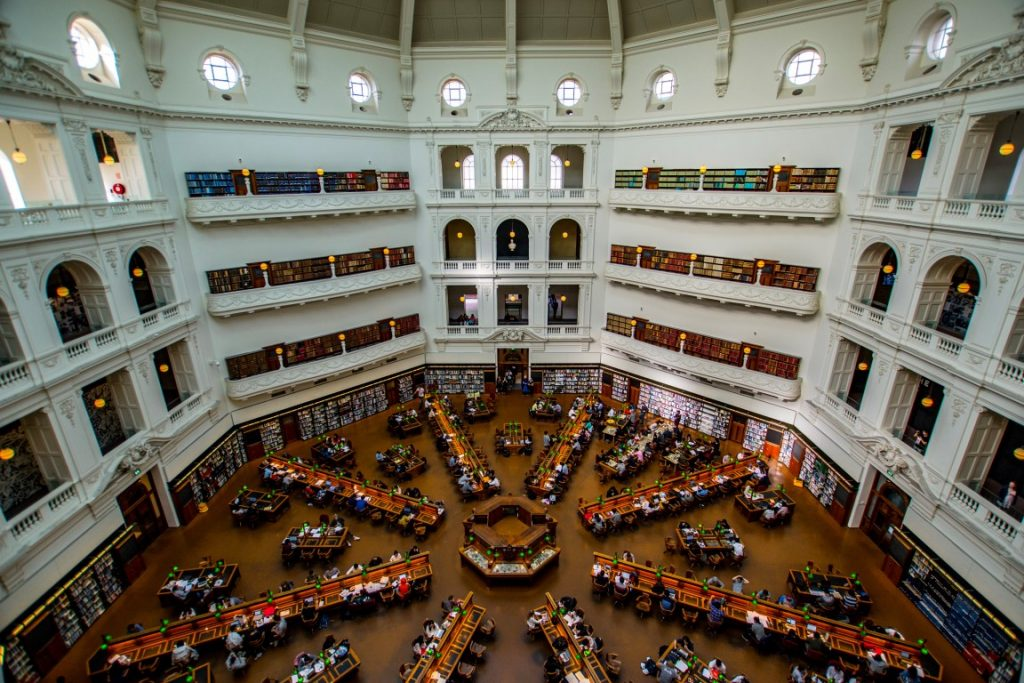 A huge old fashioned room with people reading at rows of desks on the ground floor