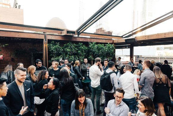 A crowd of people talking and drinking in a rooftop bar