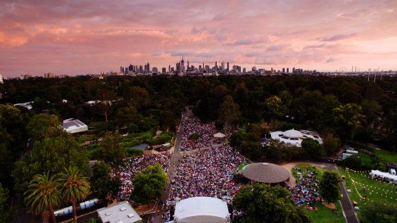 An aerial view of a big crowd of people gathered around a stage in a park