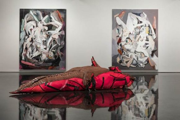 Two abstract paintings on a white wall with a lizard-esque figure on the floor in front of them.