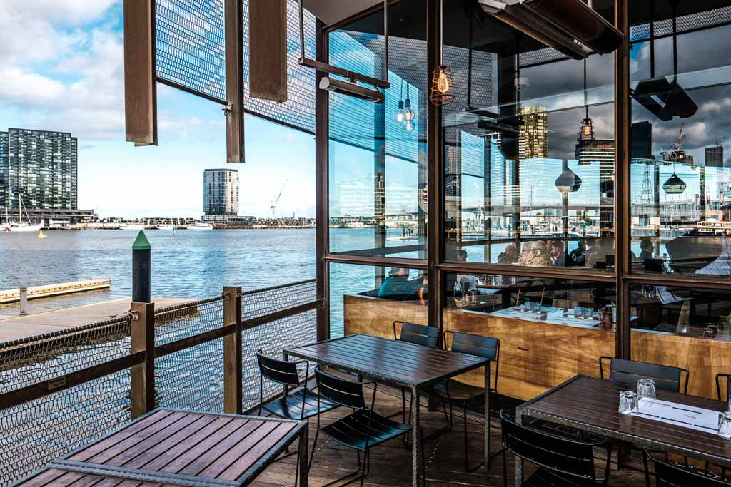 A balcony restaurant with a river view