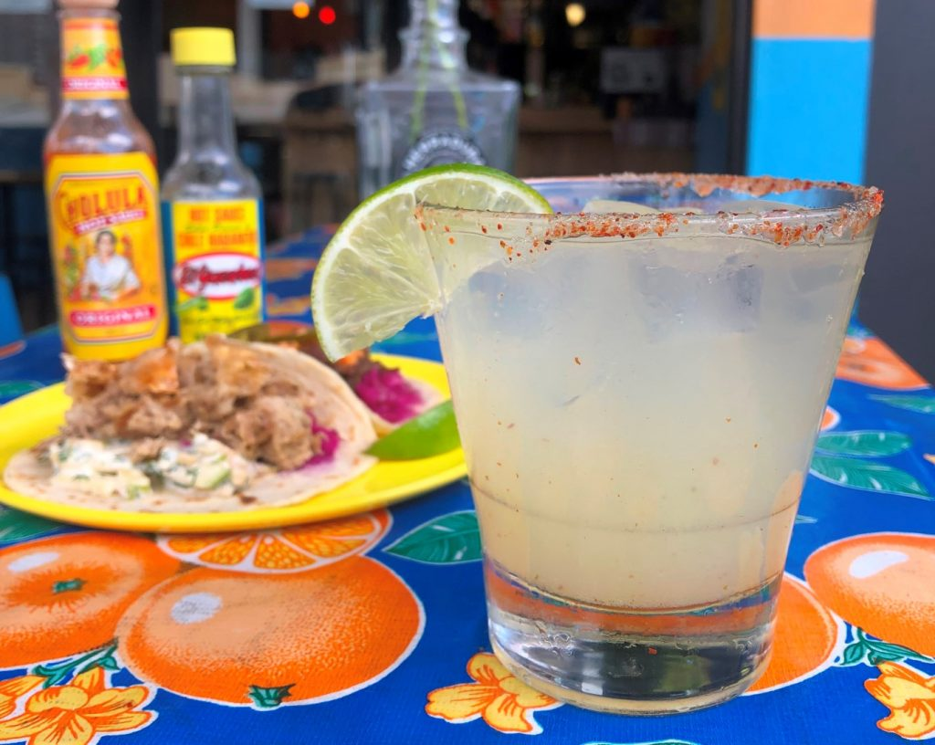 A margarita on a colourful table cloth with Mexican food in the background