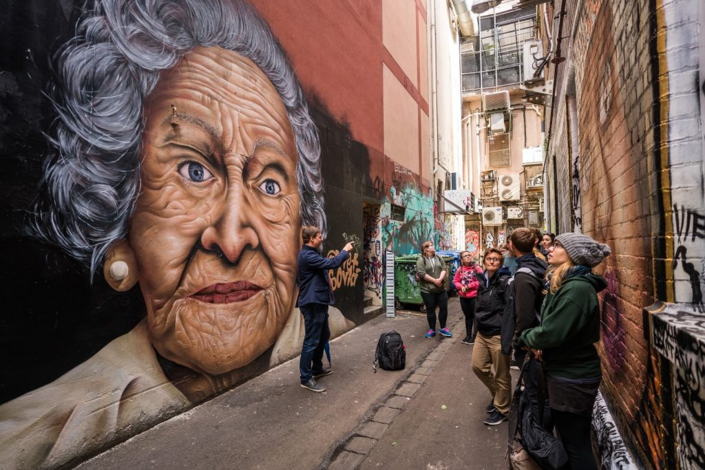 A group of people looking at street art of an older lady in a laneway