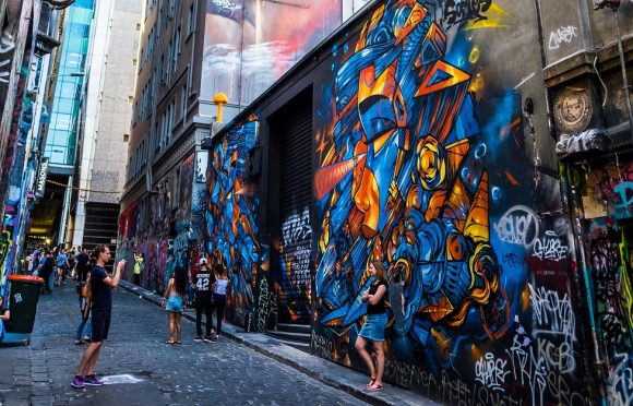 A large street art mural in a laneway, with a woman posing in front