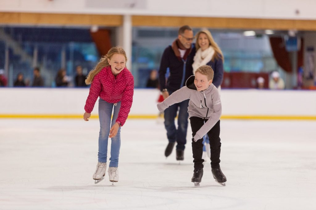 Two kids ice skating in front of another person at an indoor ice skating rink