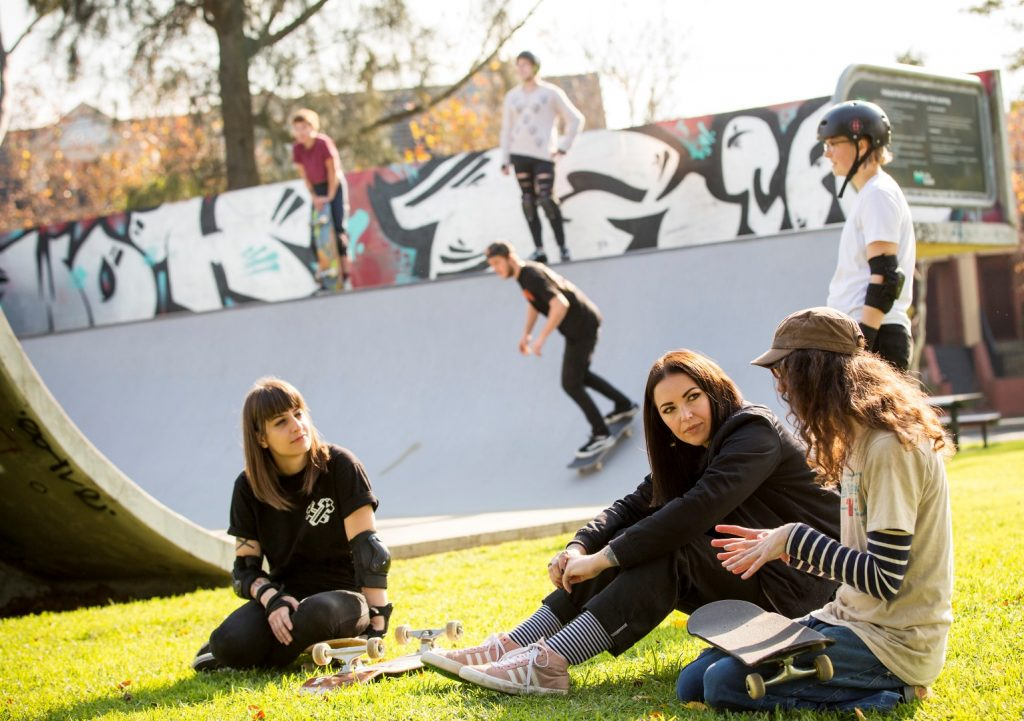 Three girls sitting on some grass in front of a half pipe at a skate park