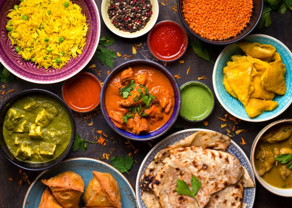 Assorted Sri Lankan food on dark wooden background. Dishes and appetizers of indian cuisine. Curry, butter chicken, rice, lentils, paneer, samosa, naan, chutney, spices. Bowls and plates with Sri Lankan food