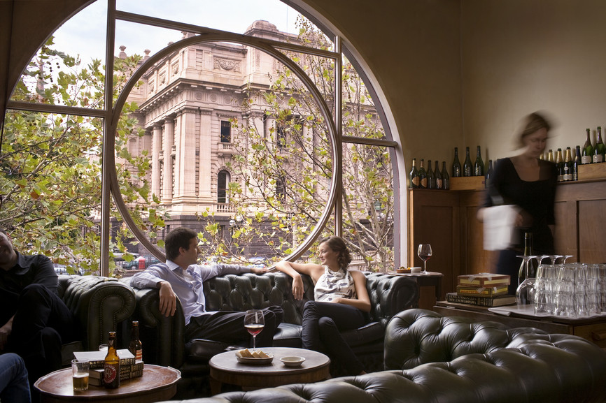 Two people drinking in a bar in front of a big window overlooking an old building
